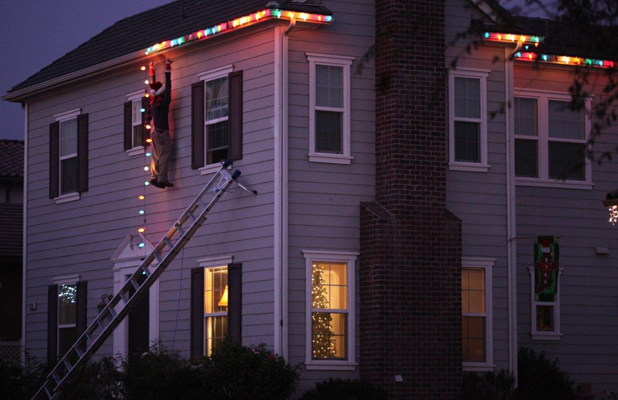 Fake Man Falling Off Roof Fitting Christmas Lights