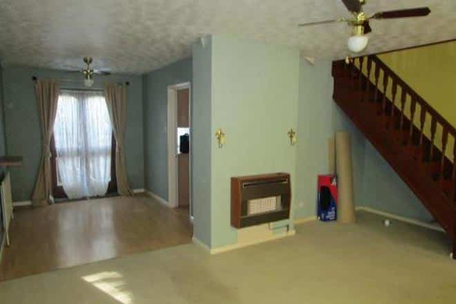 empty living room with gas fireplace and fan