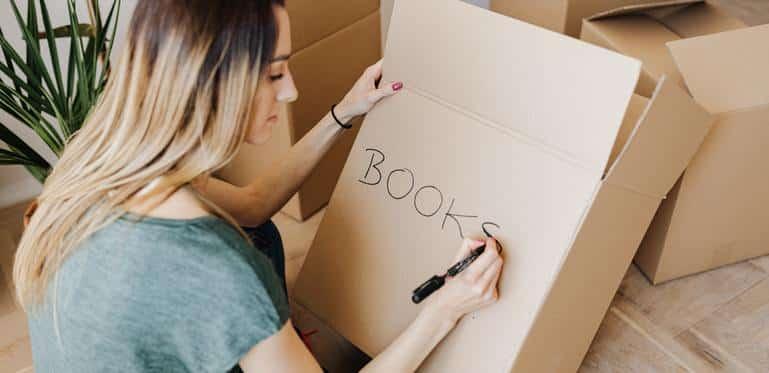 woman singin a box of books