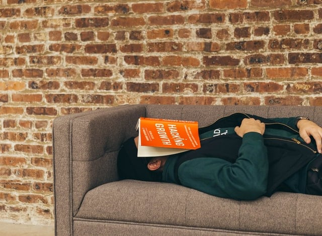 man on sofa with book over face looking asleep